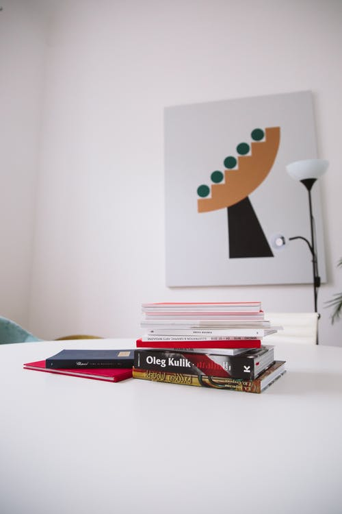 Photo Of Piled Books On White Desk