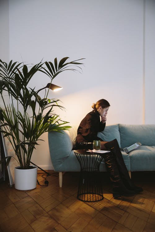 Photo Of Woman Sitting On Grey Sofa