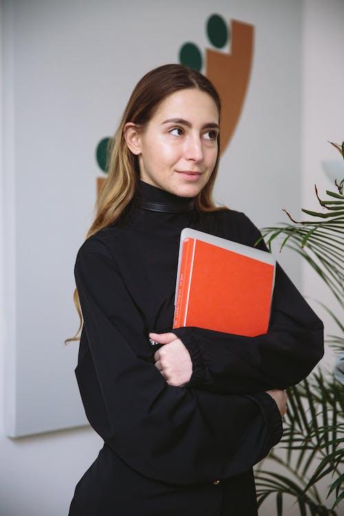 Photo Of Woman Holding Orange Book
