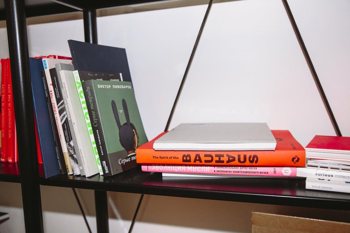 Photo Of Books Piled On Book Shelf