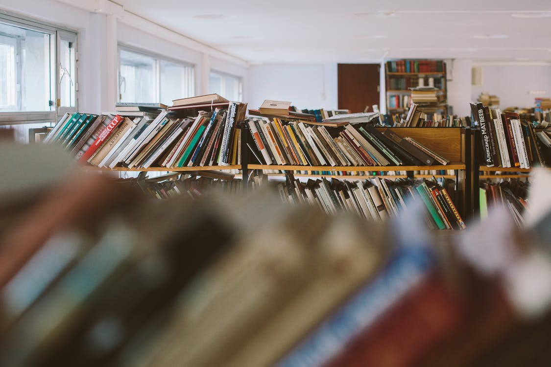 Research Books on Brown Wooden Shelf