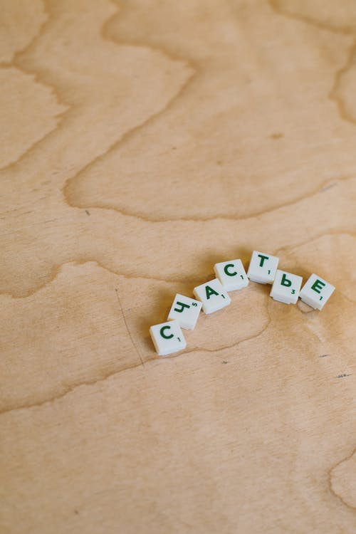 Photo Of Scrabble Pieces On Wooden Surface