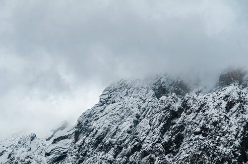 Majestic view of snowy steep mountain range covered with clouds in overcast weather