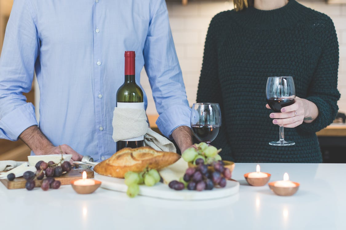 Man Standing Beside Woman Holding Wine Glass in Front of Grapes and Bread on Table