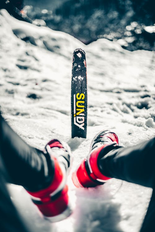 Person in Black Pants and Red and White Sneakers Riding on Snowboard
