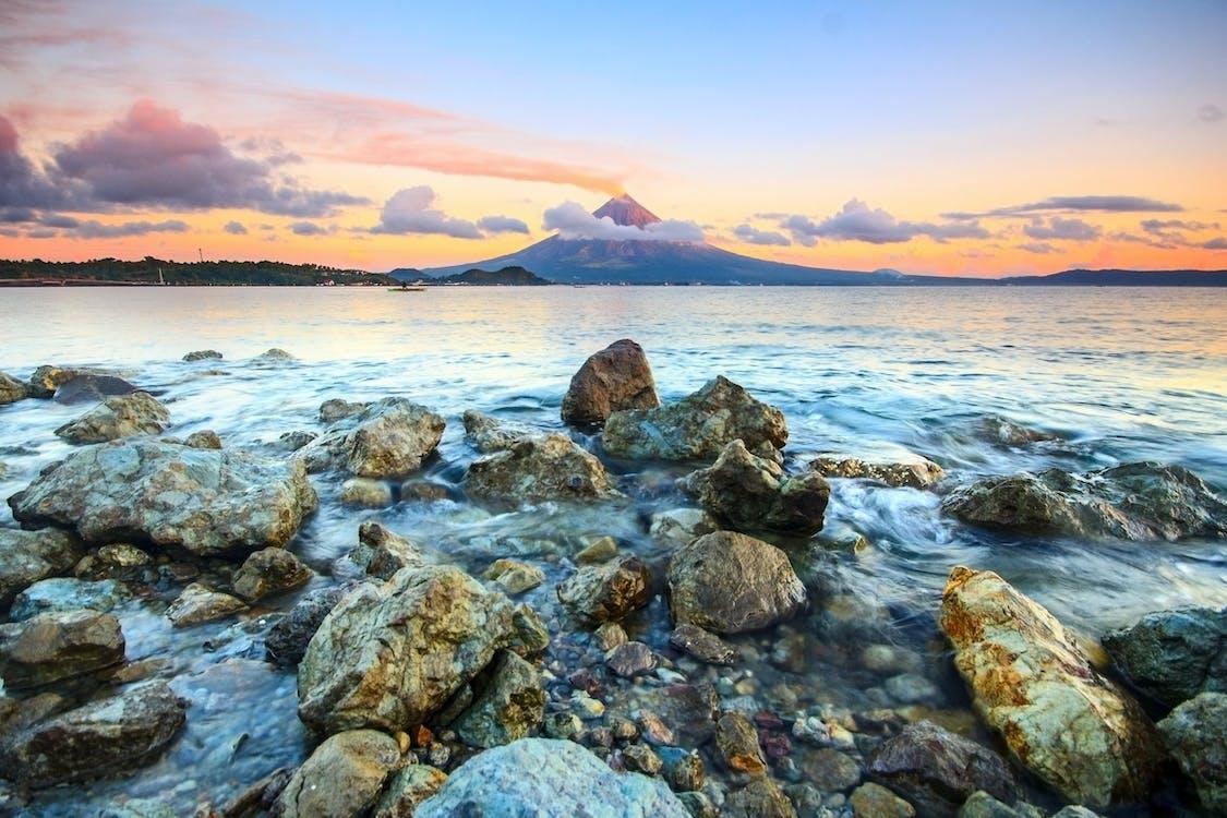 Braune Und Graue Felsen An Der Küste Während Des Sonnenuntergangs