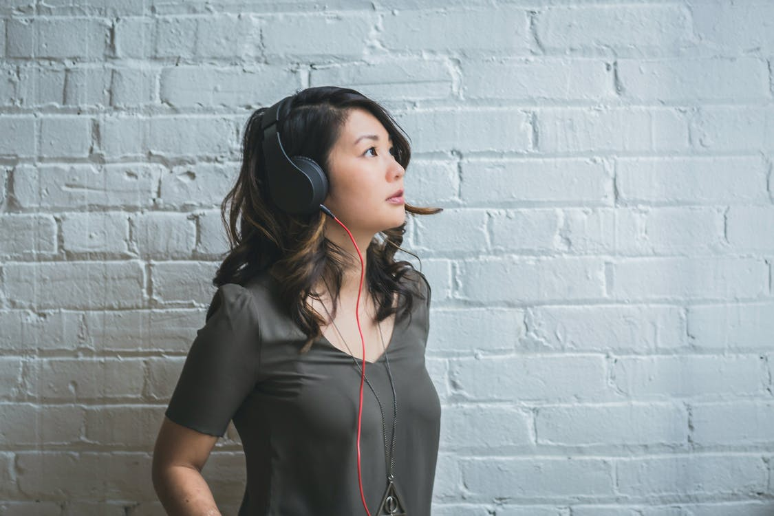 Woman Looking Up While Wearing Headphones