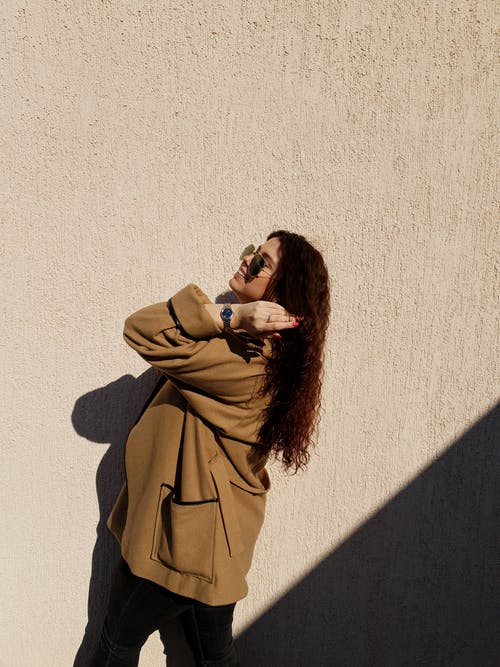 Woman in Brown Coat Near Concrete Wall