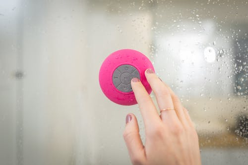 Person Holding Pink and Gray Button