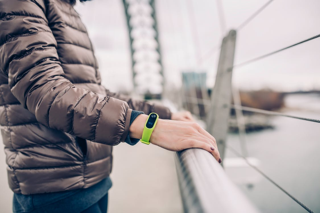 Selective Focus Photography of Man in Bubble Jacket Wearing Xiaomi Mi Band 2 Fitness Band While Holding Bridge Rails