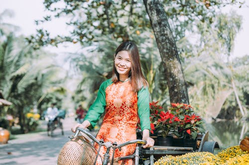 Woman in Green Long Sleeve Shirt Riding Bicycle