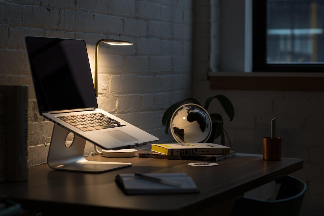 Macbook Pro on Stand Beside Desk Globe