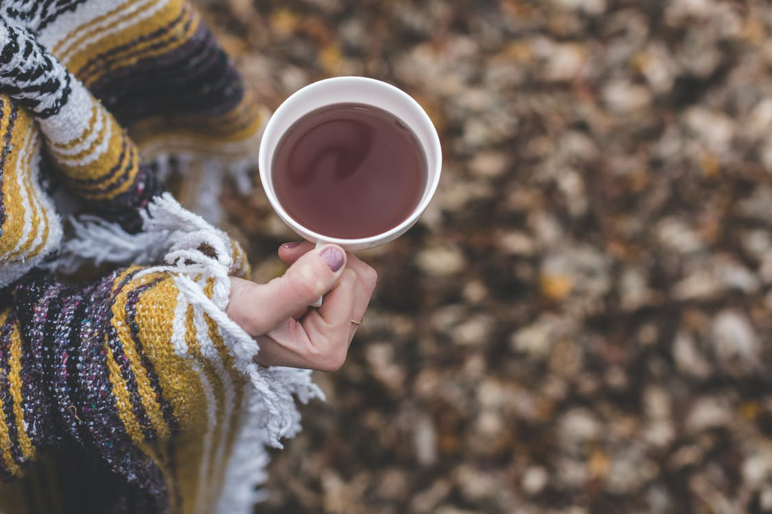 Person Holding Cup of Tea