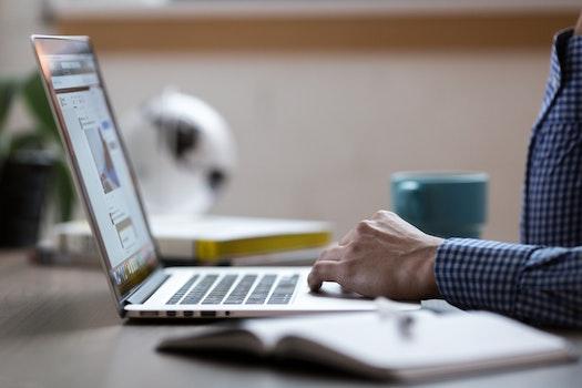 Kostenloses Stock Foto zu person, hand, schreibtisch, laptop