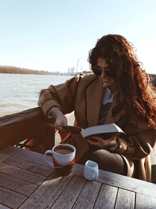Woman in Brown Coat Sitting on Brown Wooden Dock