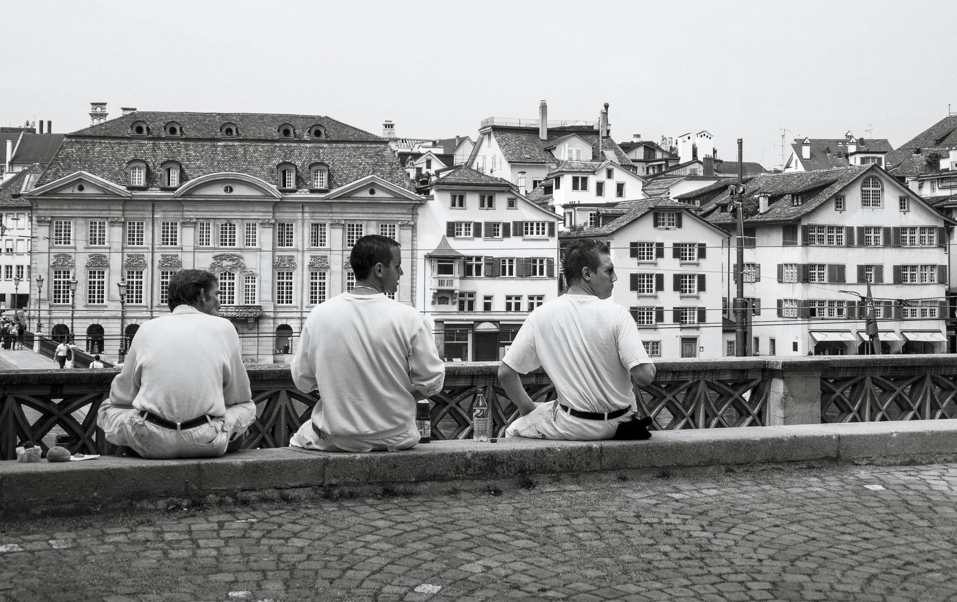 Grayscale Photography of Three Mans Sitting Near High-rise Building