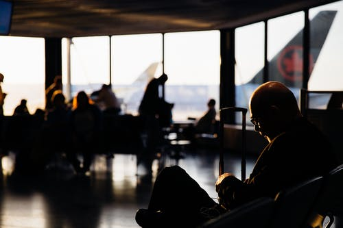 Silhouette of People Sitting Waiting to Board