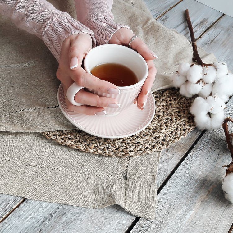 Person Holding White Ceramic Teacup With Brown Liquid