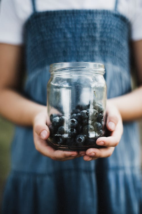 Person Holding Clear Glass Jar With Blueberries