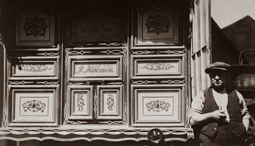 Grayscale Photo of Man Standing Beside A Wooden Wall With Carvings