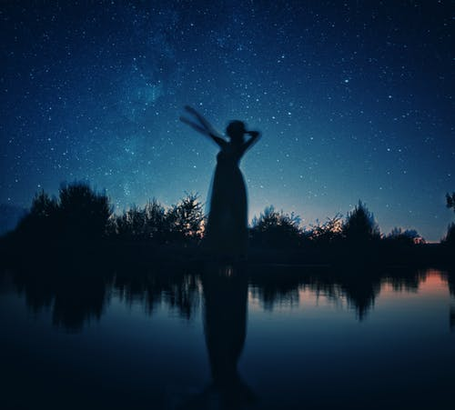 Silhouette of Woman Standing on Rock Near Body of Water during Night Time