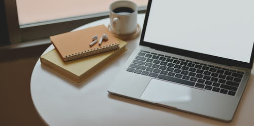 Laptop on Round Table Beside Cup of Coffee