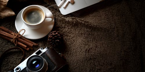 Black Dslr Camera on White Ceramic Cup and Saucer
