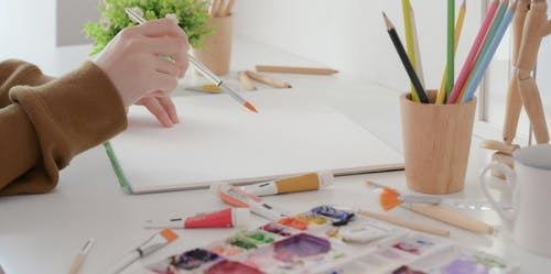 Person Holding Pen Writing on White Paper