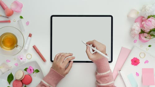 Person Holding White Pen and White Tablet