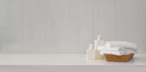 Bathroom interior with soap dispensers and towels on white table