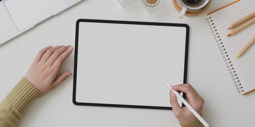 Faceless artist working on digitizing tablet with empty screen indoors