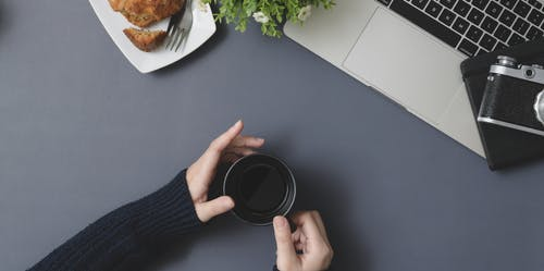 Person Holding Black Ceramic Cup