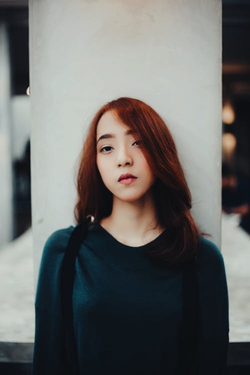 Serious young Asian female with red hair in casual clothes standing near white column and looking at camera