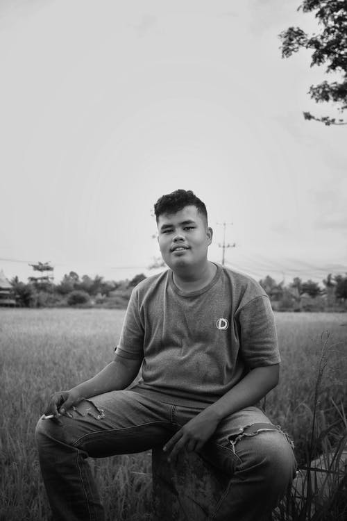 Black and white shot of ethnic teenage boy in casual clothes sitting on stump in field and looking at camera
