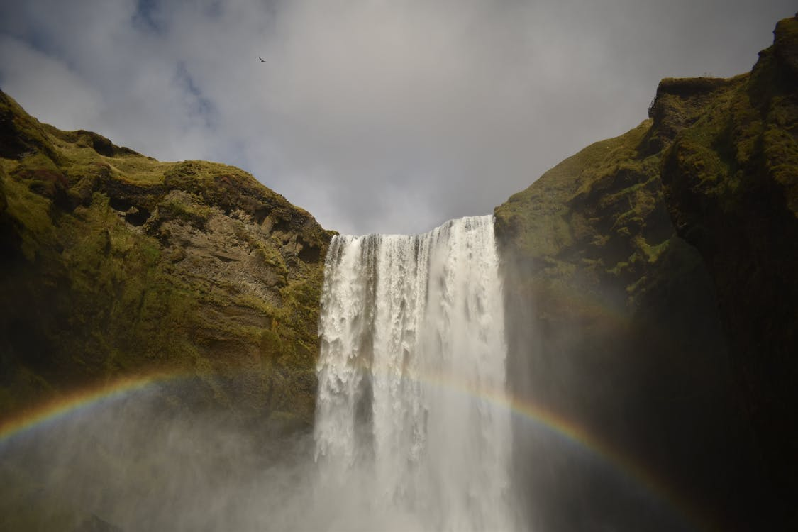Waterfalls on Green and Brown Mountain Under White Clouds