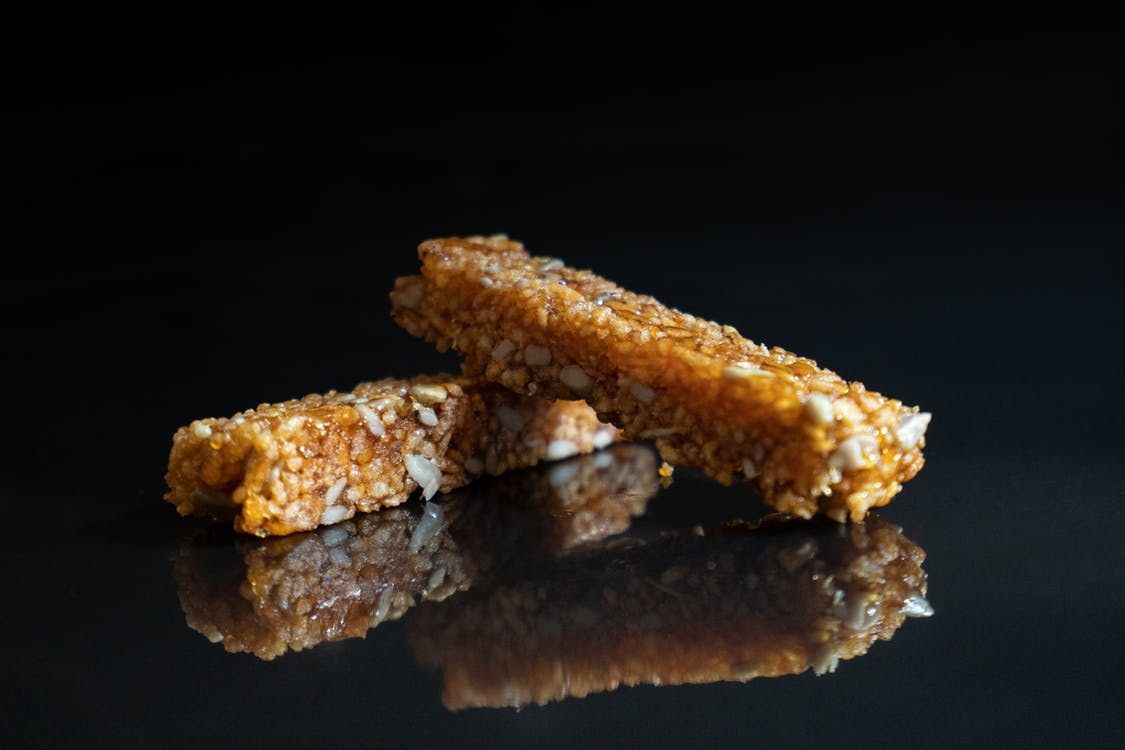 Delicious nut brittle placed on black surface