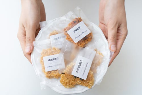 Person Holding Brown Rice in Pack