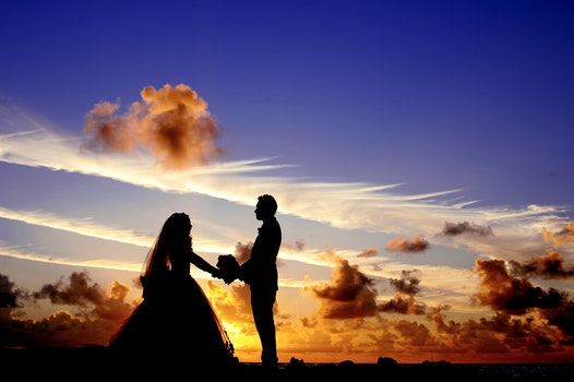 Silhouette of Wedding Couple Holding Hands Under Cloudy Blue Sky