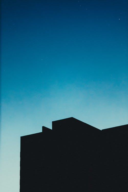 Silhouette of modern house against blue night sky