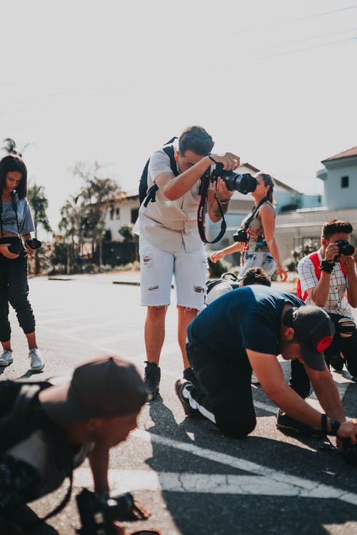 Group of multiethnic people in casual clothes with photo cameras taking photos on road in street of modern suburb on sunny day