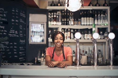 Photo of Smiling Bartender Leaning on Counter