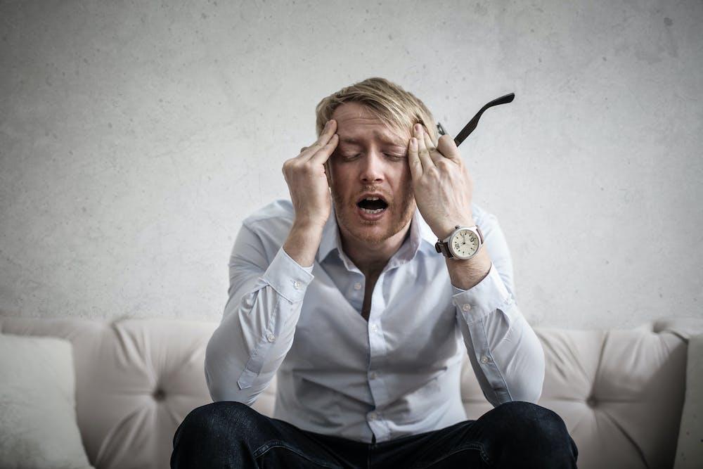 A man touches his head.   Photo: Pexels