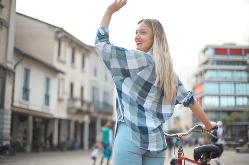 Back View Photo of Smiling Woman in Checkered Shirt and Blue Denim Jeans Standing with a Bicycle Waving