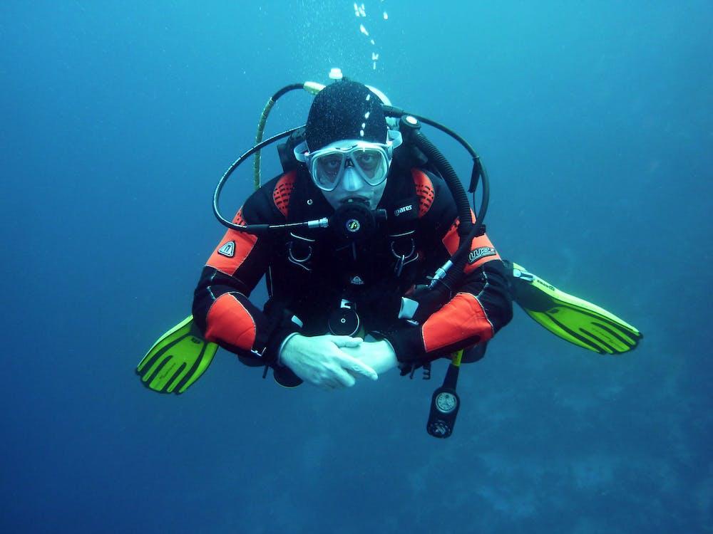Human in Black Orange Swimming Suit in Blue Body of Water