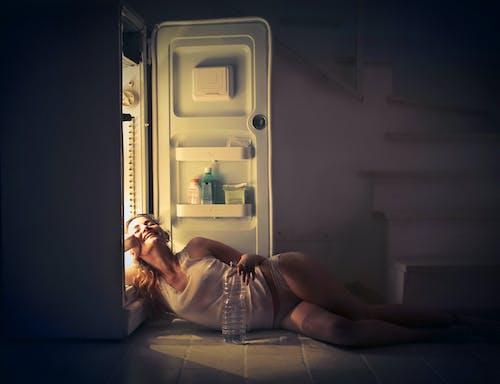 Photo De Femme Souriante En Gilet Blanc Et Culotte Allongée Sur Le Sol à Côté D'un Réfrigérateur Ouvert Avec Les Yeux Fermés