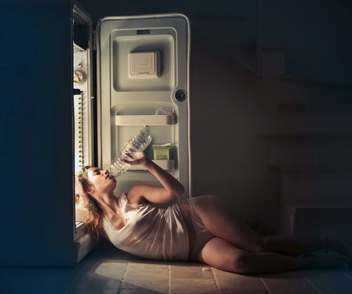 Photo of Woman in White Vest and Panties Lying on Floor Next to Open Fridge While Drinking Water from Plastic Bottle