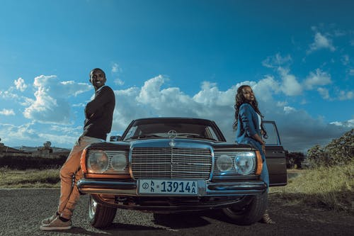 Stylish black couple standing near retro car in countryside