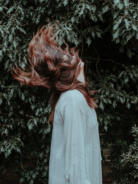Side View Photo of Woman in White Long Sleeve Dress Standing Near Green-leafed Plant Doing Hair Flip