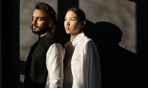 Uomo In Camicia Nera Accanto A Donna In Camicia Bianca