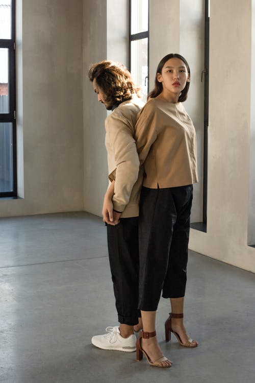Man and Woman in Beige Long Sleeve Shirt and Black Pants Standing Back to Back